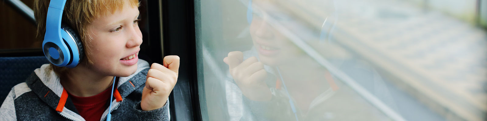 Autism - ASD - Autistic Child with headphones on train - Communicating Above Barriers